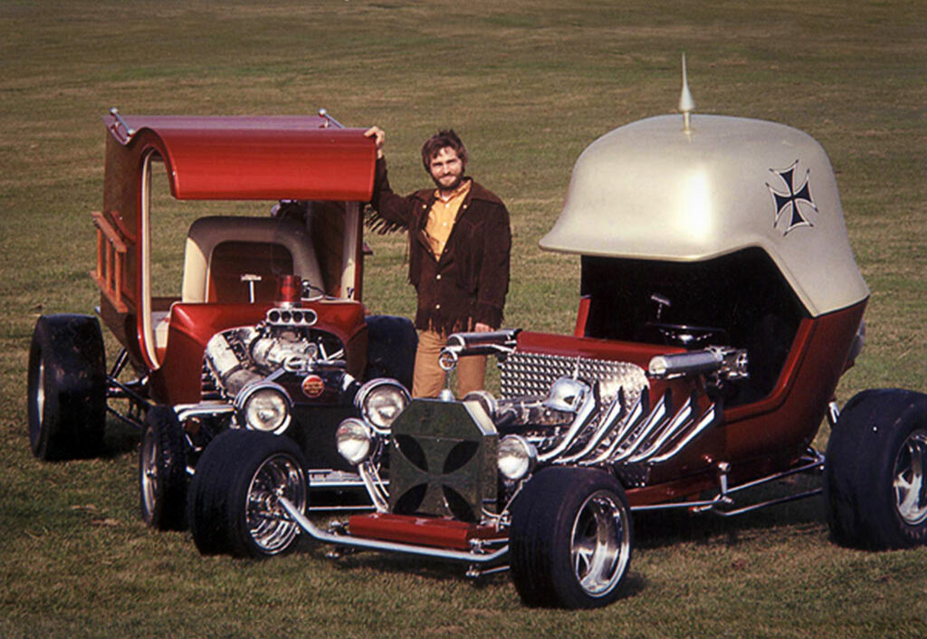 Chuck Miller standing with his renowned Fire Engine Co. No. 13 and Red Baron Roadster, circa 1970.